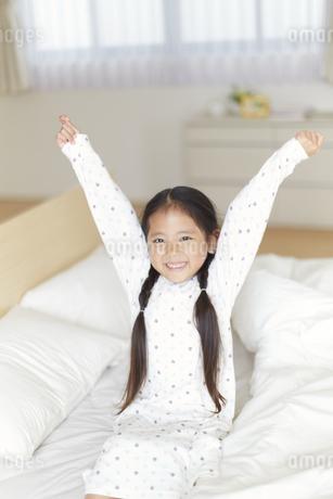 ベットの上で伸びをするパジャマ姿の女の子の写真素材 [FYI02967059]