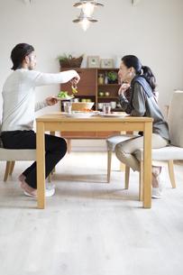 椅子に座ってサラダを取り分ける男性と微笑む女性の写真素材 [FYI02967063]