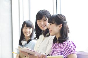 教室の窓際で教材を持って会話する女子学生たちの写真素材 [FYI02967064]
