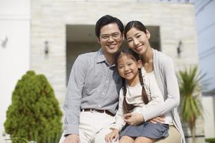家の前でほほ笑む3人家族の写真素材 [FYI02967066]