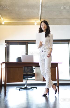 オフィスで資料を手に持ち微笑むビジネス女性の写真素材 [FYI02967067]