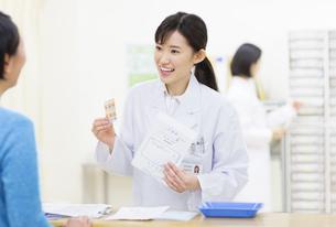 薬の説明をする女性薬剤師と患者の写真素材 [FYI02967069]