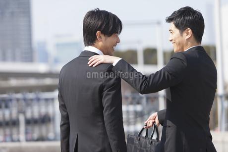 肩に手をかけて笑い合うビジネス男性2人の写真素材 [FYI02967074]
