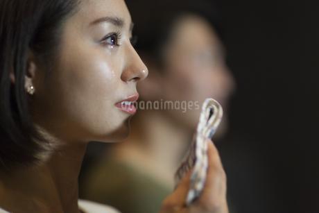 映画館で涙をこぼす女性の写真素材 [FYI02967081]
