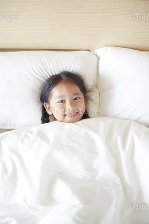 布団から顔だけ出して微笑む女の子の写真素材 [FYI02967093]