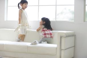ソファーの上で笑う2人の女の子の写真素材 [FYI02967095]
