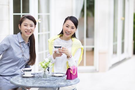 コーヒーを飲みながら遠くを見て笑う2人の女性の写真素材 [FYI02967102]