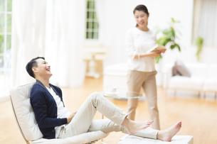 部屋でリラックスして笑い合う夫婦の写真素材 [FYI02967103]