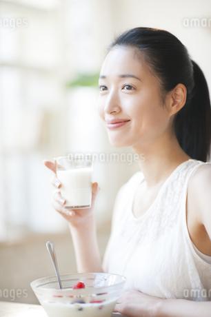 牛乳を手に微笑む女性の写真素材 [FYI02967110]