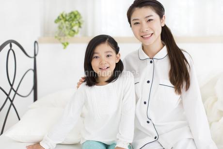 ベットに掛けて笑う母と娘の写真素材 [FYI02967111]