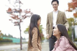 見つめ合って微笑む母娘と見守るお父さんの写真素材 [FYI02967112]