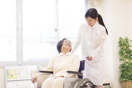 車椅子の患者に添う女性看護師の写真素材 [FYI02967115]