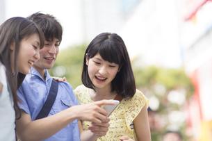 街中でスマートフォンを見て微笑む3人の若者の写真素材 [FYI02967120]