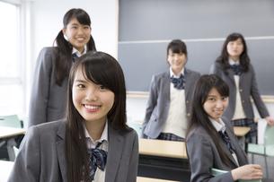 教室の席に座って微笑む女子高校生たちのポートレートの写真素材 [FYI02967127]