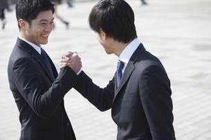 笑顔で手を組むビジネス男性2人の写真素材 [FYI02967134]