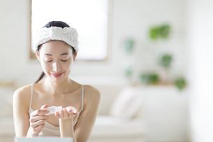 コットンに美容液を湿らす女性の手の写真素材 [FYI02967139]