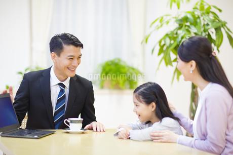 説明する訪問営業の男性と話を聞く母と娘の写真素材 [FYI02967141]