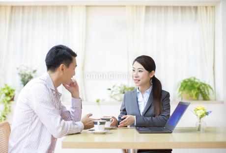 説明する訪問営業の女性と話を聞く男性の写真素材 [FYI02967144]