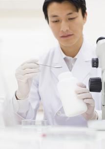 薬さじを使って研究をしている男性研究員の写真素材 [FYI02967145]