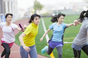 陸上競技場でバトンの手渡しをする女子学生たちの写真素材 [FYI02967146]