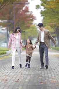 遊歩道で両親と手をつないで喜ぶ女の子の写真素材 [FYI02967151]