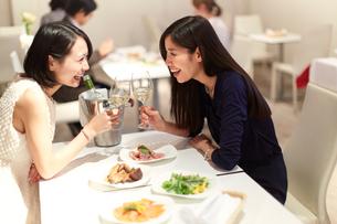 レストランでワインを手に笑い合う女性二人の写真素材 [FYI02967153]