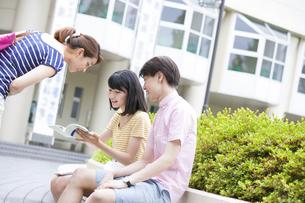キャンパスで参考書を覗き込む学生たちの写真素材 [FYI02967155]