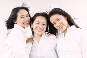 風を受けながら笑う女性3人の写真素材 [FYI02967159]