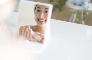 鏡の前でスキンケアをする微笑む女性の写真素材 [FYI02967160]