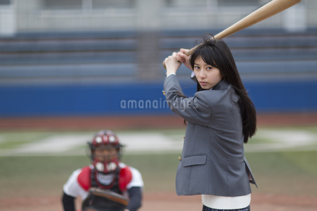 野球バットを持って打つ構えをする女子学生の写真素材 [FYI02967166]