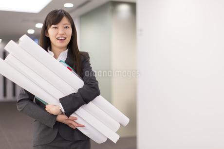筒を抱えて笑うビジネス女性の写真素材 [FYI02967168]