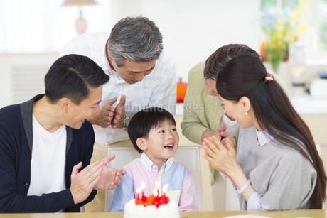 ケーキを前に誕生日のお祝いをする家族の写真素材 [FYI02967171]