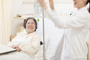 点滴を準備する女性看護婦と話をする患者の写真素材 [FYI02967177]