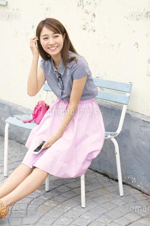 ベンチに座って微笑む女性の写真素材 [FYI02967180]