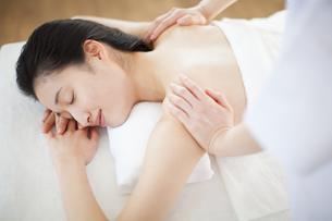 うつ伏せで肩をマッサージされている女性の写真素材 [FYI02967181]