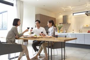 ホームパーティでワインを手に会話する男女三人の写真素材 [FYI02967187]