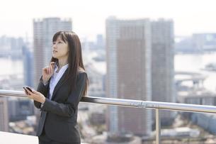屋上でスマートフォンを手に考えるビジネス女性の写真素材 [FYI02967193]