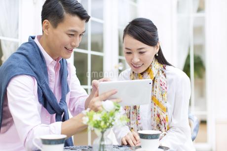屋外のテーブルでタブレットPCを見るカップルの写真素材 [FYI02967194]
