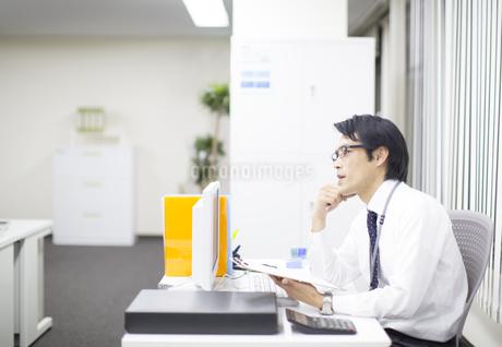 デスクで考えるビジネス男性の写真素材 [FYI02967196]
