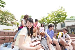 キャンパスで笑う女子学生と友達の学生たちの写真素材 [FYI02967197]