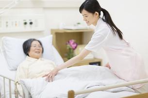 患者に布団をかける女性看護師の写真素材 [FYI02967199]