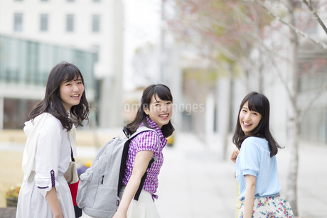 キャンパスで笑顔で振り向く女子学生たちの写真素材 [FYI02967200]
