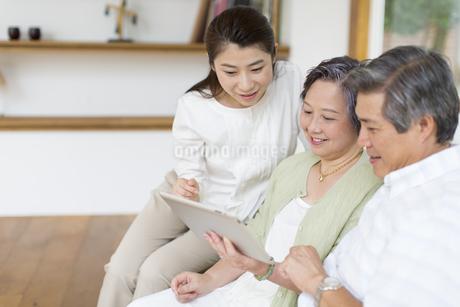 タブレットPCを見るシニア夫婦と娘の写真素材 [FYI02967201]