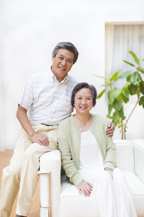 ソファーで微笑むシニア夫婦の写真素材 [FYI02967202]