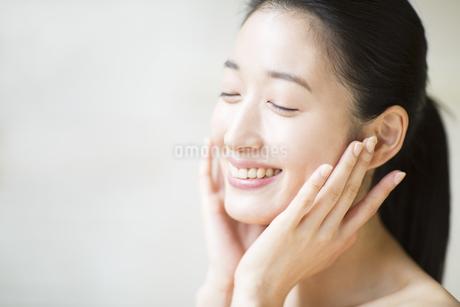 頬に両手を添えて目を瞑り微笑む女性の写真素材 [FYI02967204]