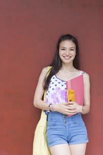 赤い壁の前で微笑む女子学生のポートレートの写真素材 [FYI02967205]