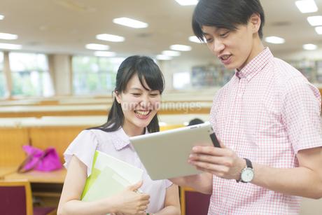 スマートデバイスを見る男女の学生の写真素材 [FYI02967207]