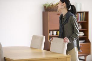 椅子に手をついて微笑む女性の写真素材 [FYI02967214]