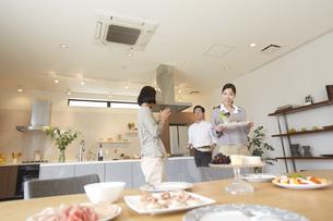テーブルに食事を運ぶ女性と会話する男女の写真素材 [FYI02967220]