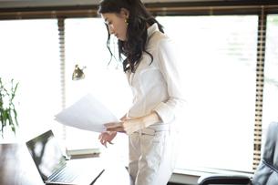 オフィスのデスクで資料を手に持つビジネス女性の写真素材 [FYI02967224]